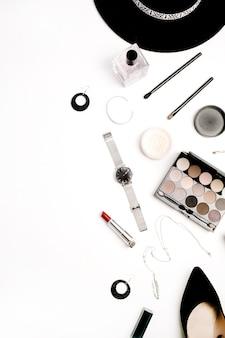 Weibliches modeaccessoires und kosmetikkonzept. hut, schuhe, palette, lippenstift, uhren, puder auf weißem hintergrund. flache lage, ansicht von oben