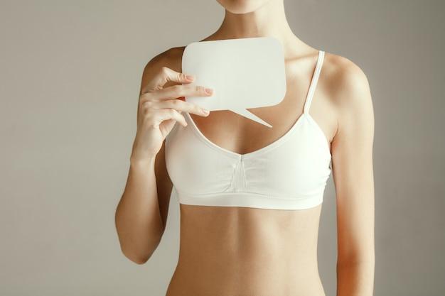 Weibliches model, das leere karte in der nähe von brüsten hält