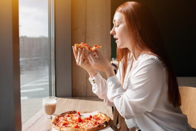 Weibliches model hält ein stück pizza in den händen. junge frau, die pizza im café isst.