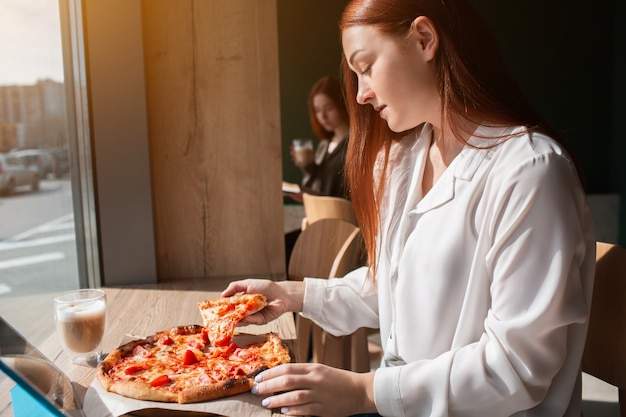 Weibliches model hält ein stück pizza in den händen. junge frau, die pizza isst.