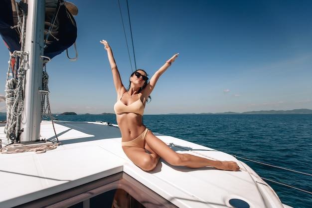 Weibliches model im bikini und mit sonnenbrille sitzt auf ihrer riesigen weißen yacht und hebt die hände und schaut in den himmel.