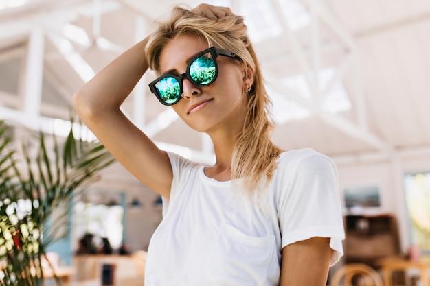 Weibliches model in trendigem t-shirt und stylischer funkelnder sonnenbrille.