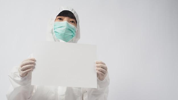 Weibliches model mit psa-suite und gesichtsmaske und zwei händen mit handschuhen hält a4-papier auf weißem hintergrund.