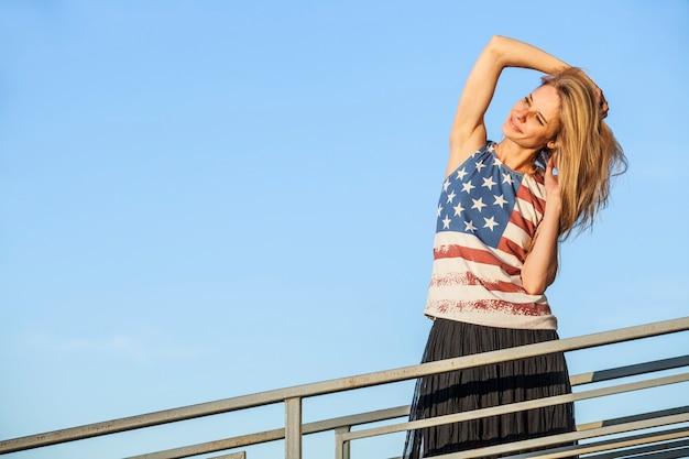 Weibliches modell auf der oberfläche des blauen himmels in einem t-shirt mit der amerikanischen flagge