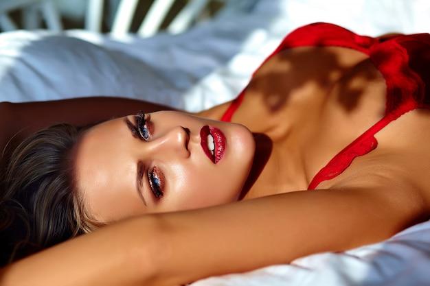 Weibliches modell, das am morgen rote wäsche auf dem bett trägt