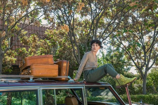Weibliches modell, das auf einem auto sitzt, das für ein fotoshooting mit suticases zur seite aufwirft