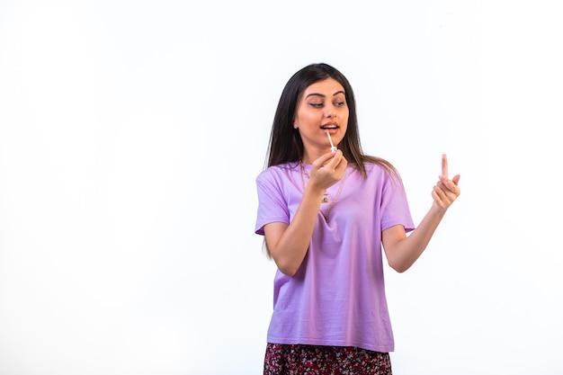 Weibliches modell, das lippenprodukte fördert und sie anwendet