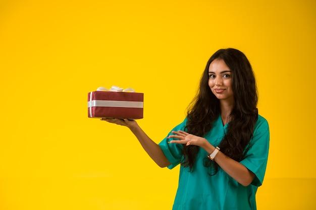 Weibliches modell, das mit einer geschenkbox aufwirft.