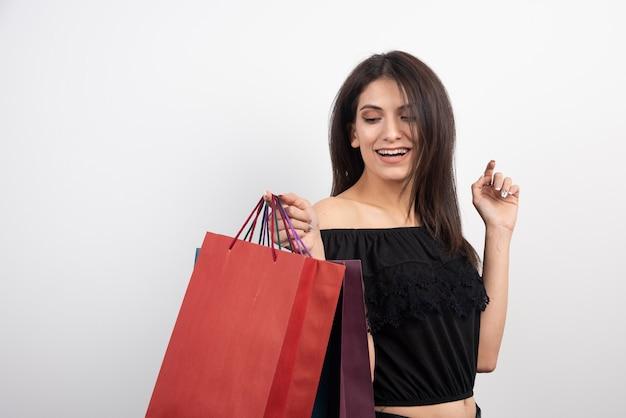 Weibliches modell, das mit einkaufstaschen aufwirft