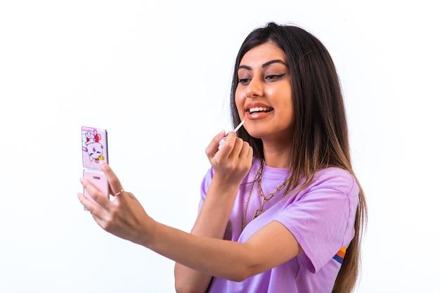 Weibliches modell, das täglichen lipgloss anwendet, während es zum spiegel schaut