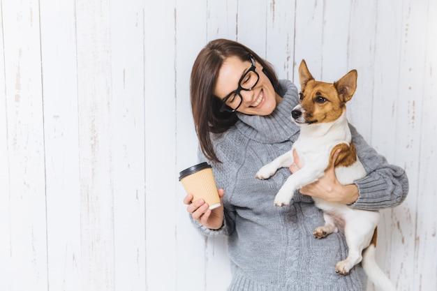Weibliches modell des glücklichen brunette trägt warme gestrickte strickjacke, gläser, trägt ihren lieblingshund und mitnehmerkaffee