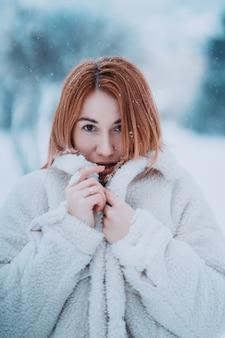 Weibliches modell des porträts draußen im ersten schnee