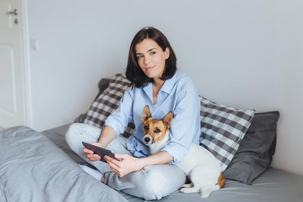 Weibliches modell des träumerischen brunette in den pyjamas sitzt gekreuzte beine auf bequemem bett im schlafzimmer, hält moderne tablette, umfasst ihr haustier