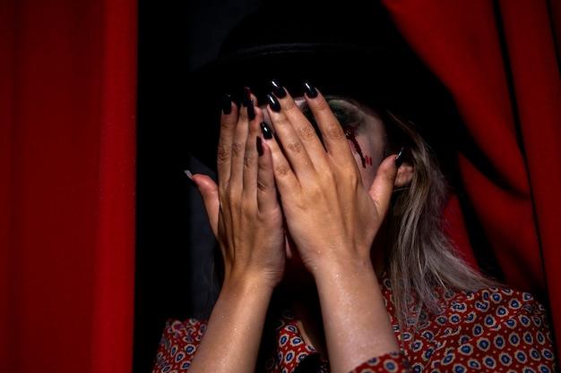 Weibliches modell halloweens, das ihr gesicht versteckt