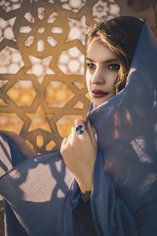 Weibliches modell im grauen hijab in der moschee