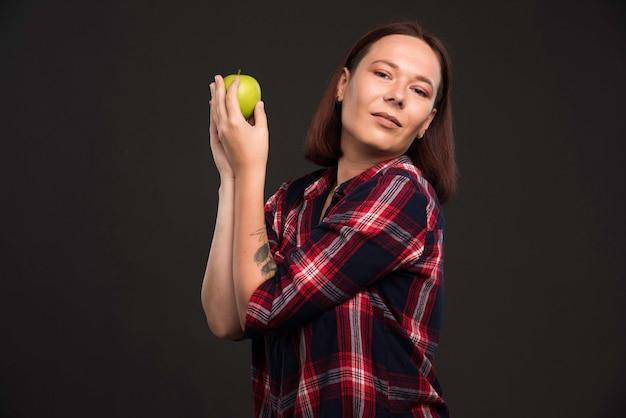 Weibliches modell im herbst winterkollektion outfits hält einen grünen apfel und genießt es.