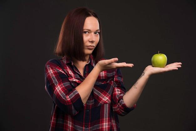 Weibliches modell im herbst winterkollektion outfits hält einen grünen apfel und zeigt darauf.