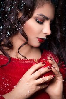 Weibliches modell im roten kleid, das einen granatapfel hält