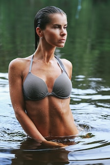 Weibliches modell im schwarzen badeanzug im see