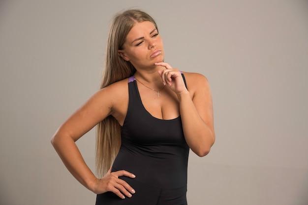Weibliches modell im sport-bh sieht mit den händen am kinn verführerisch aus.