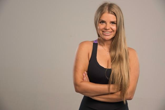 Weibliches modell im sport-bh sieht mit geschlossenen händen verführerisch aus