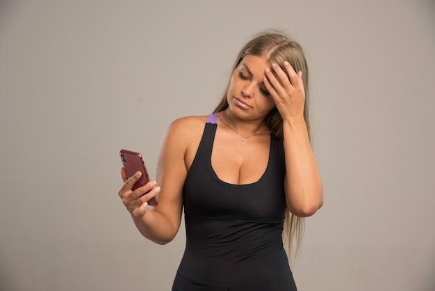 Weibliches modell im sport-bh sms mit ihrem smartphone und sieht müde aus.
