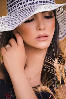 Weibliches modell im weißen designhut und im sommer make-up