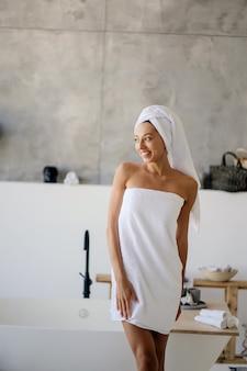 Weibliches modell im weißen handtuch. frauen-, schönheits- und hygienekonzept.