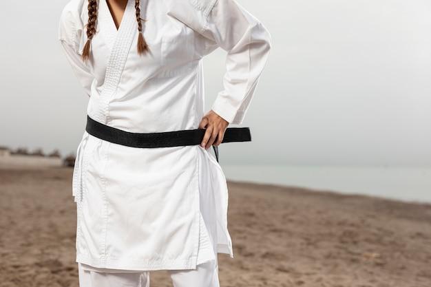 Weibliches modell in der karateausstattung mit gurt