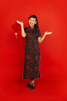 Weibliches modell in traditioneller kleidung sieht glücklich aus und lächelt mit dekoration