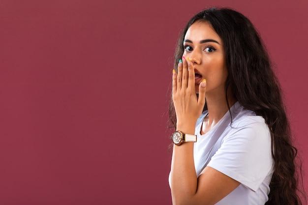 Weibliches modell macht überraschtes gesicht auf rosa wand