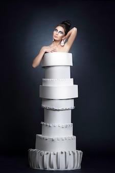 Weibliches modell mit frisur und make-up, die ein papierkleid tragen, über schwarzem hintergrund.