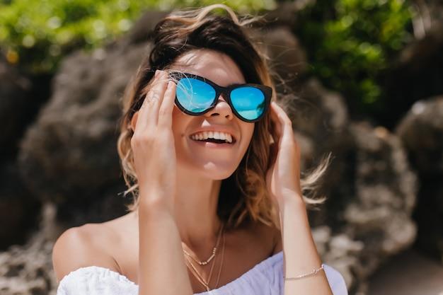 Weibliches modell mit gebräunter haut, die himmel betrachtet und lacht. positive kaukasische frau in funkelnder sonnenbrille, die guten sommertag genießt.