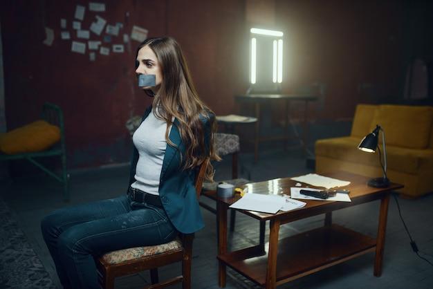 Weibliches opfer eines verrückten entführers mit aufgeklebtem mund und einem seil. entführung ist ein schweres verbrechen, entführung horror, gewalt