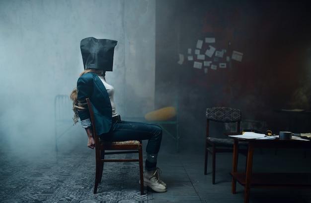 Weibliches opfer eines verrückten entführers mit einer tasche auf dem kopf. entführung ist ein schweres verbrechen, entführung horror, gewalt