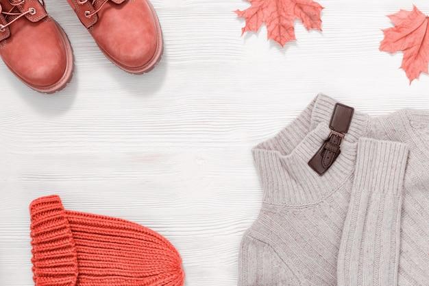 Weibliches outfit, stiefel, strickpullover und mütze.