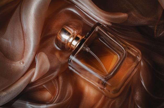 Weibliches parfüm auf rosa stoff