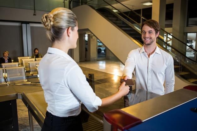 Weibliches personal, das am check-in-schalter eine bordkarte gibt