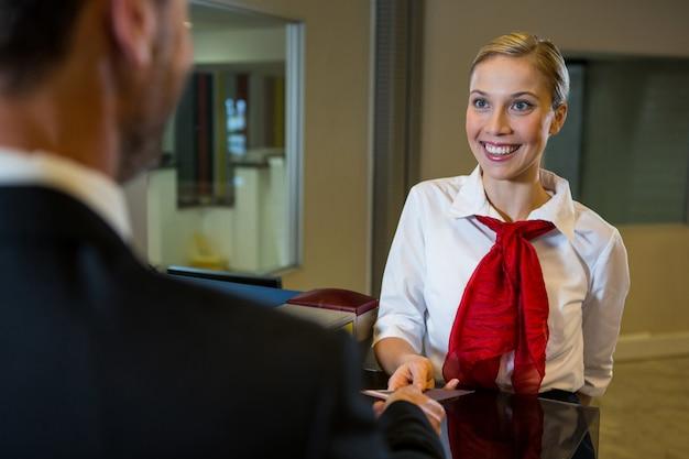 Weibliches personal, das dem geschäftsmann eine bordkarte gibt