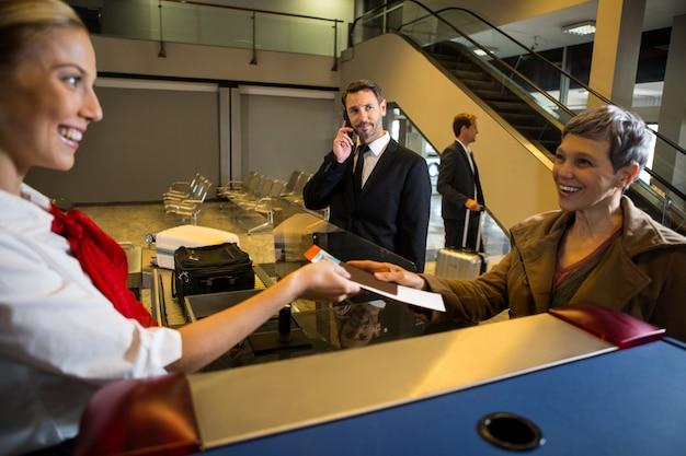 Weibliches personal, das dem passagier eine bordkarte gibt