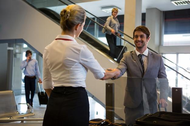 Weibliches personal, das die bordkarte der passagiere am check-in-schalter überprüft