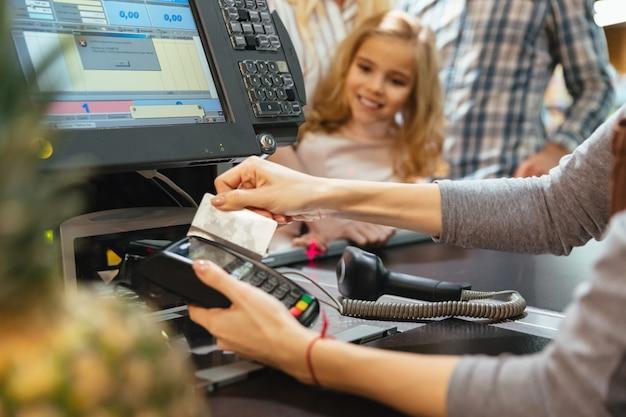 Weibliches personal, das kreditkartenterminal am geldschalter verwendet