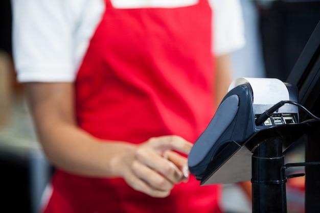 Weibliches personal, das kreditkartenterminal am kassenschalter benutzt