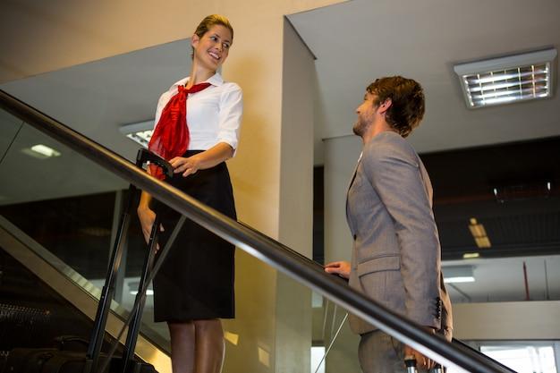 Weibliches personal, das mit geschäftsmann auf rolltreppe interagiert