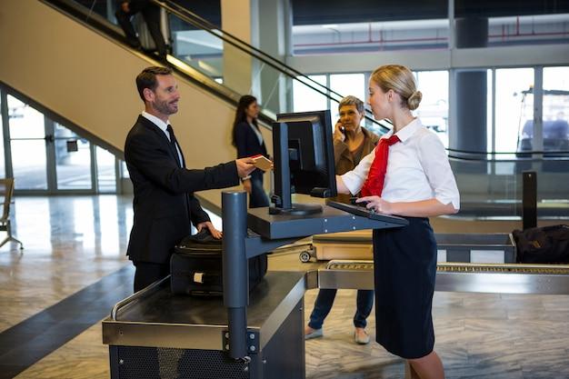 Weibliches personal, das mit passagier interagiert