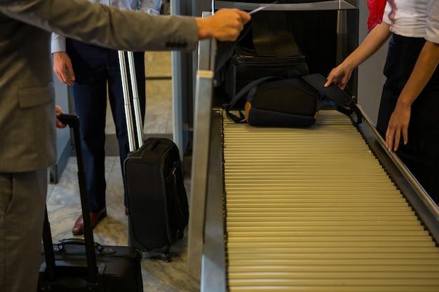Weibliches personal, das passagiergepäck auf förderband überprüft