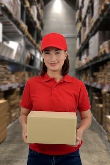 Weibliches personal heben von paketboxen im lager