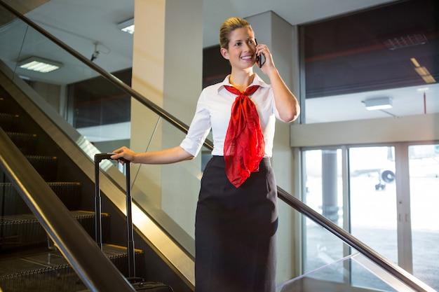 Weibliches personal mit gepäck, das auf mobiltelefon auf rolltreppe spricht