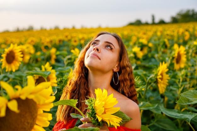 Weibliches porträt der jungen frau im feld der blühenden sonnenblumen in den strahlen des sonnenuntergangs süßes mädchen von cauca...