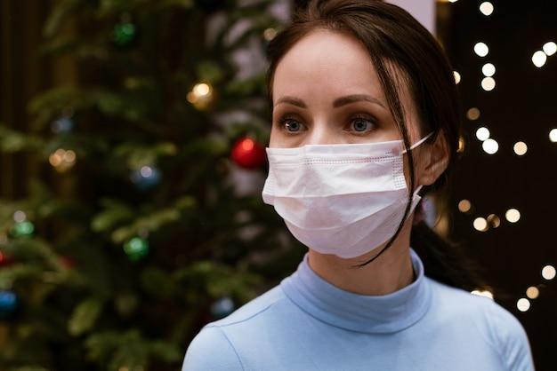 Weibliches porträt der kaukasischen frau in der medizinischen maske auf bokeh lichtern